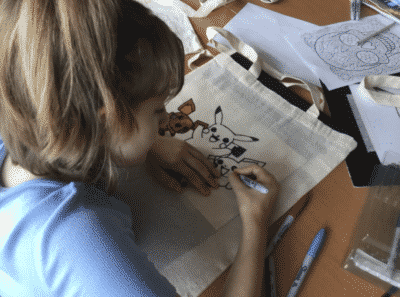 child drawing on tote bag